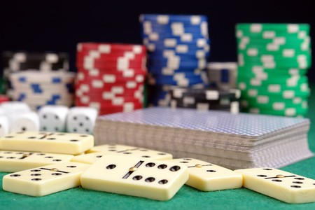 Pile of domino pieces, deck of playing cards, dices and casino chips on green tablecloth Stock Photo - 4056513