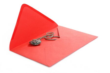 Red envelope with heart-shaped necklet over white photo