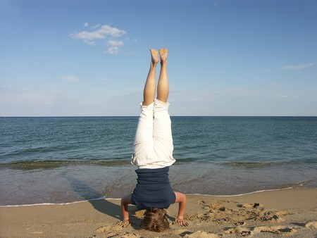 headstand: Woman doing a headstand on a beach Stock Photo