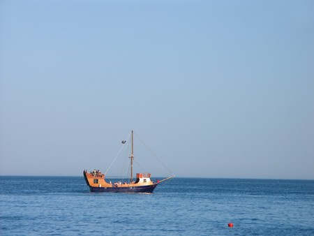 anchoring: Tourist boat with holiday makers on board anchoring near the seashore Stock Photo