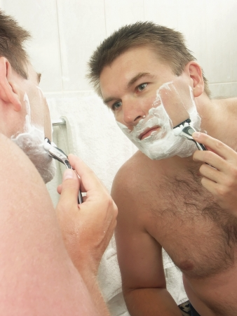 Young man shaving his face in bathroom with razor photo