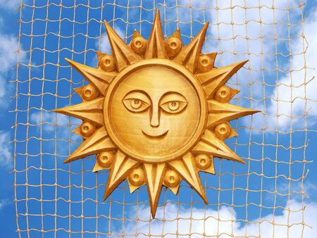 fishermans net: Wooden carved sun suspended on a fishermans net against blue sky with clouds