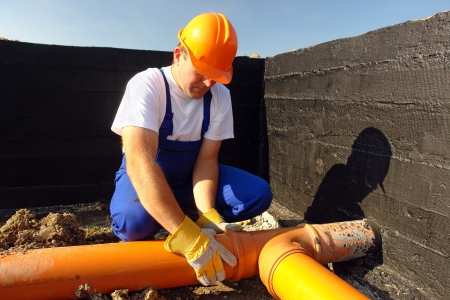 riool: Loodgieter montage pvc rioleringsbuizen in huis stichting Stockfoto