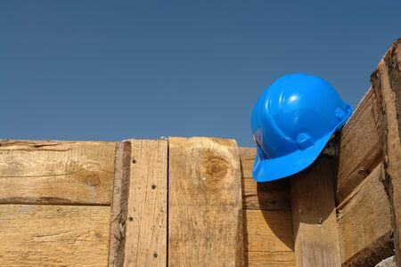 affixed: Blue helmet affixed to the wooden shuttering wall