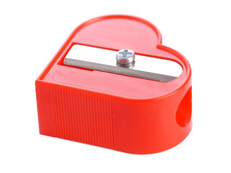 pencil sharpener: Red plastic heart-shaped pencil sharpener over white background Stock Photo