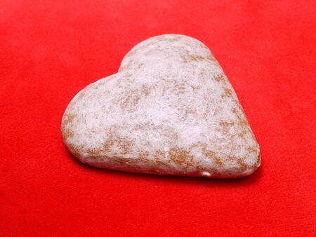 adoration: Heart-shaped gingerbread cake shot over red background