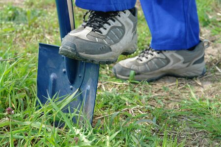 Closeup of construction workers leg driving shovel into ground photo