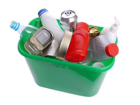 Green plastic trash bin filled with assorted domestic garbage - over white background