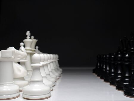 chessmen: Rows of white and black set of chessmen standing face to face over black background