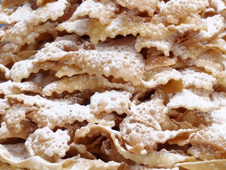 surfeit: Closeup shot of traditional Polish sweet crispy biscuits called Faworki with caster sugar