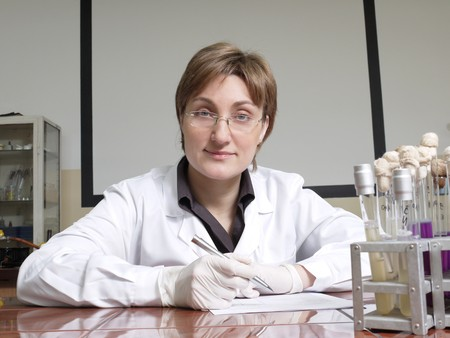 specimen testing: Retrato de la mujer sentada detr�s de t�cnico de laboratorio laboratorio escritorio con tubos de ensayo Foto de archivo