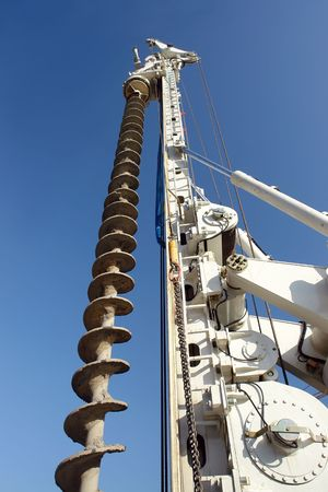driller: Closeup shot of vertical drilling rig against blue sky Stock Photo