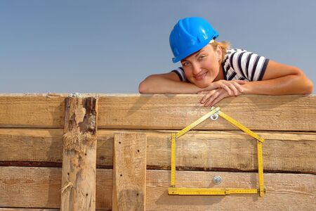 affixed: Young female wearing blue helmet posing over yellow house shaped wooden folding ruler affixed to wooden shuttering wall over blue sky Stock Photo