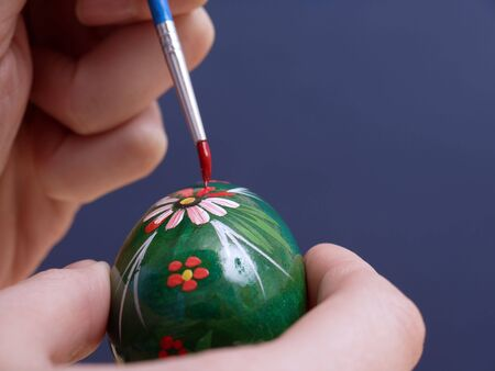Female hand painting easter egg with paintbrush photo