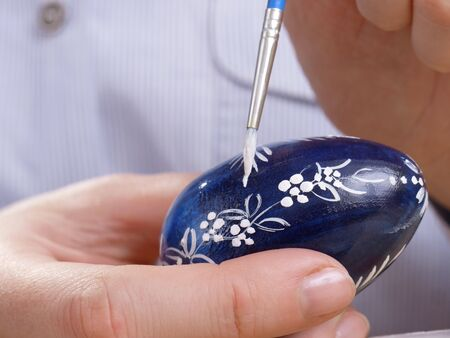 patter: Female painting easter egg in floral patter with paintbrush
