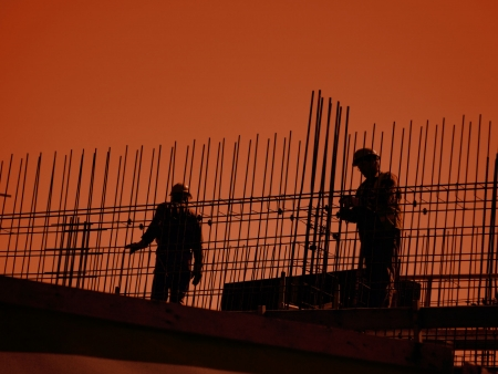 Silhouettes of construction workers working with steel reinforcement againts orange sky