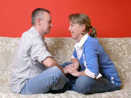 tenderly: Young happy couple sitting on sofa face-to-face, looking at each other tenderly