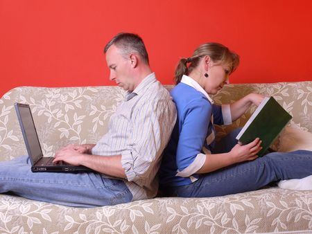 Young couple sitting on sofa back-to-back spending time together, guy working with laptop, woman reading a book Stock Photo - 4694363