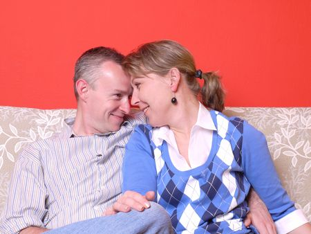 tenderly: Young happy couple sitting on sofa, looking into each other eyes tenderly
