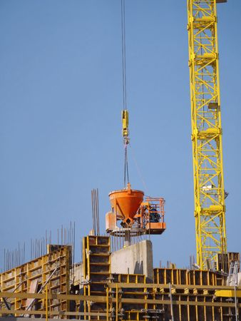 Construction worker pouring concrete mix from charging hopper transported by jib crane