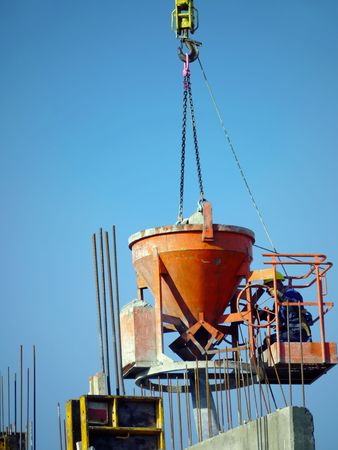hooked up: Construction worker pouring concrete mix from charging hopper platform hooked up to jib crane Stock Photo
