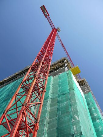 erection: Raw state residential highrise and jib crane over clear blue sky Stock Photo