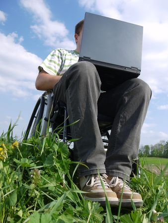 Handicapped man on wheelchair using laptop outdoors Stock Photo - 4791509