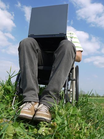 Handicapped man on wheelchair using laptop outdoors