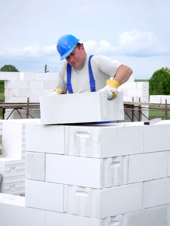 Mason building house walls from white aerated autoclaved concrete blocks photo