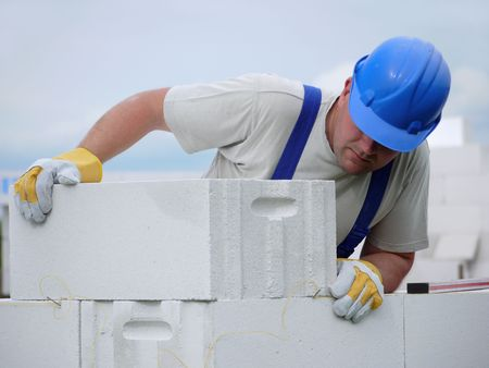 Mason aligning aerated autoclaved concrete block of constructed house wall Stock Photo