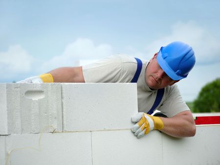 brick mason: Mason aligning aerated autoclaved concrete block of constructed house wall Stock Photo