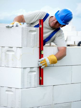 Mason checking plumb line of house wall being made from aerated autoclaved concrete blocks Stock Photo