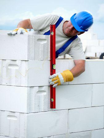 Plomada de alba�il de control de pared de casa que se realizan a partir de bloques de concreto aireado en autoclave Foto de archivo - 5014016