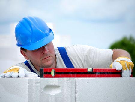 メイソン気泡オートクレーブ養生コンクリート ブロックから作られて家壁レイヤーの水平方向のレベルをチェック