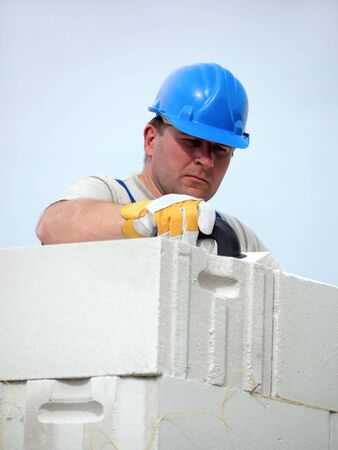 Mason applying mortar using trowel onto house wall brick layer photo