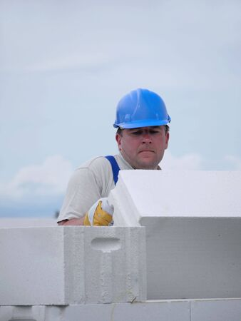 Mason laying white aerated autoclaved concrete block of a single-family house wall Stock Photo