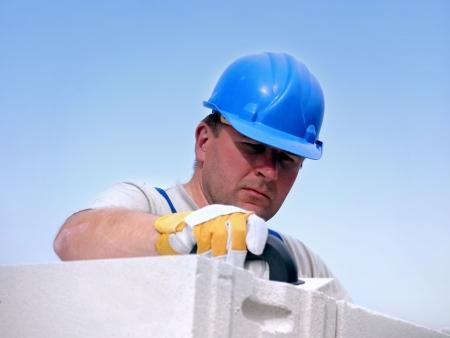 layers: Mason applying mortar using trowel onto house wall brick layer
