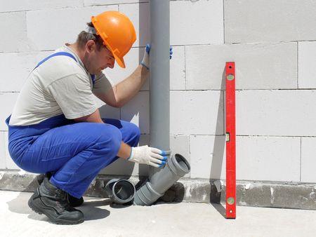 組立未完成の家の中のポリ塩化ビニールの下水管の配管工