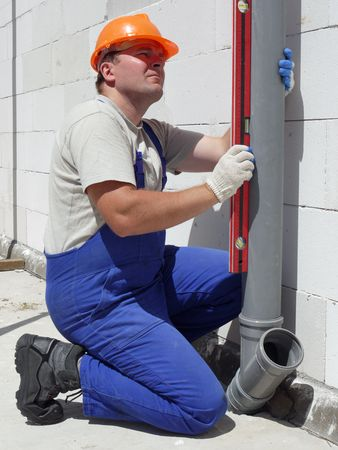 Plumber using level for checking plumb line of assembled pvc sewage pipes inside unfinished house Reklamní fotografie - 5044617