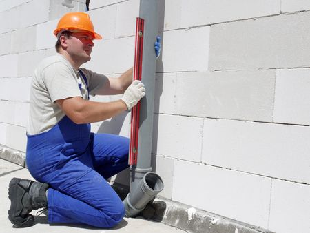 plumb: Plumber using level for checking plumb line of assembled pvc sewage pipes inside unfinished house