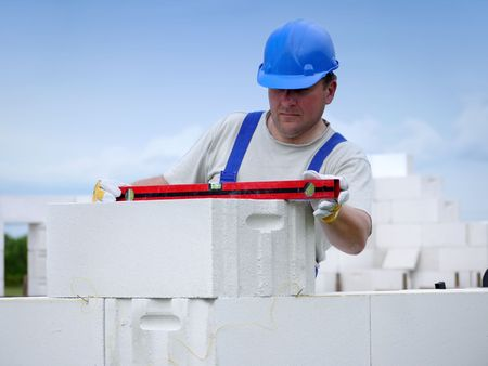 Mason checking horizontal level of house wall  layer being made from aerated autoclaved concrete blocks Stock Photo