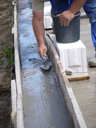 Closeup of mason spreading mortar with trowel inside wooden shuttering photo
