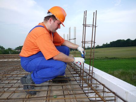 Bar bender fixing steel reinforcement for house concrete floor slab Stock Photo