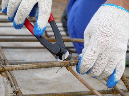Closeup shot of bar bender hands fixing steel reinforcement bars using pincers Stock Photo