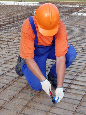 ceiling slab: Bar bender fixing steel reinforcement for house concrete floor slab Stock Photo
