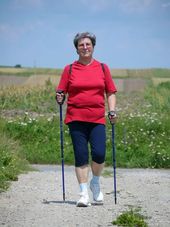 Senior woman practising nordic walking in the countryside Stock Photo