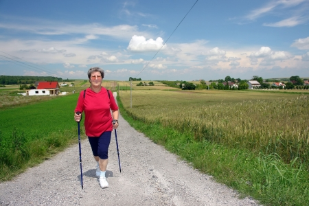 Senior woman practising nordic walking in the countryside Standard-Bild
