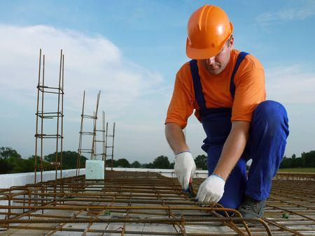 reinforcing bar: Bar bender fixing steel reinforcement for house concrete floor slab Stock Photo