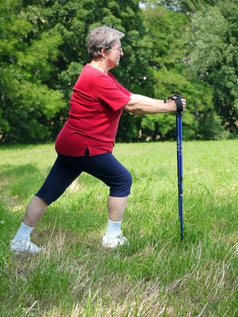 nordic country: Senior woman doing a series of warm-up exercises with walking poles