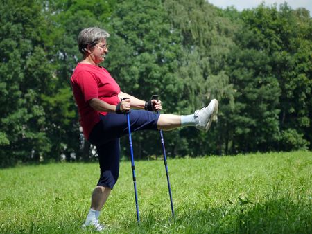 Senior woman doing a series of warm-up exercises with walking poles photo